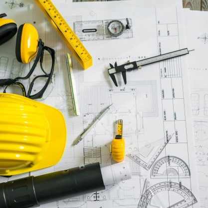 construction-plans-with-helmet-and-drawing-tools-on-blueprints_1232-4301